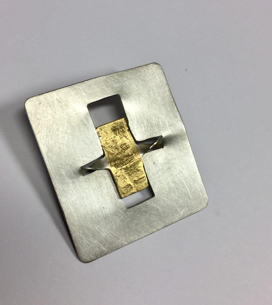 foto van een broche met puur goud.