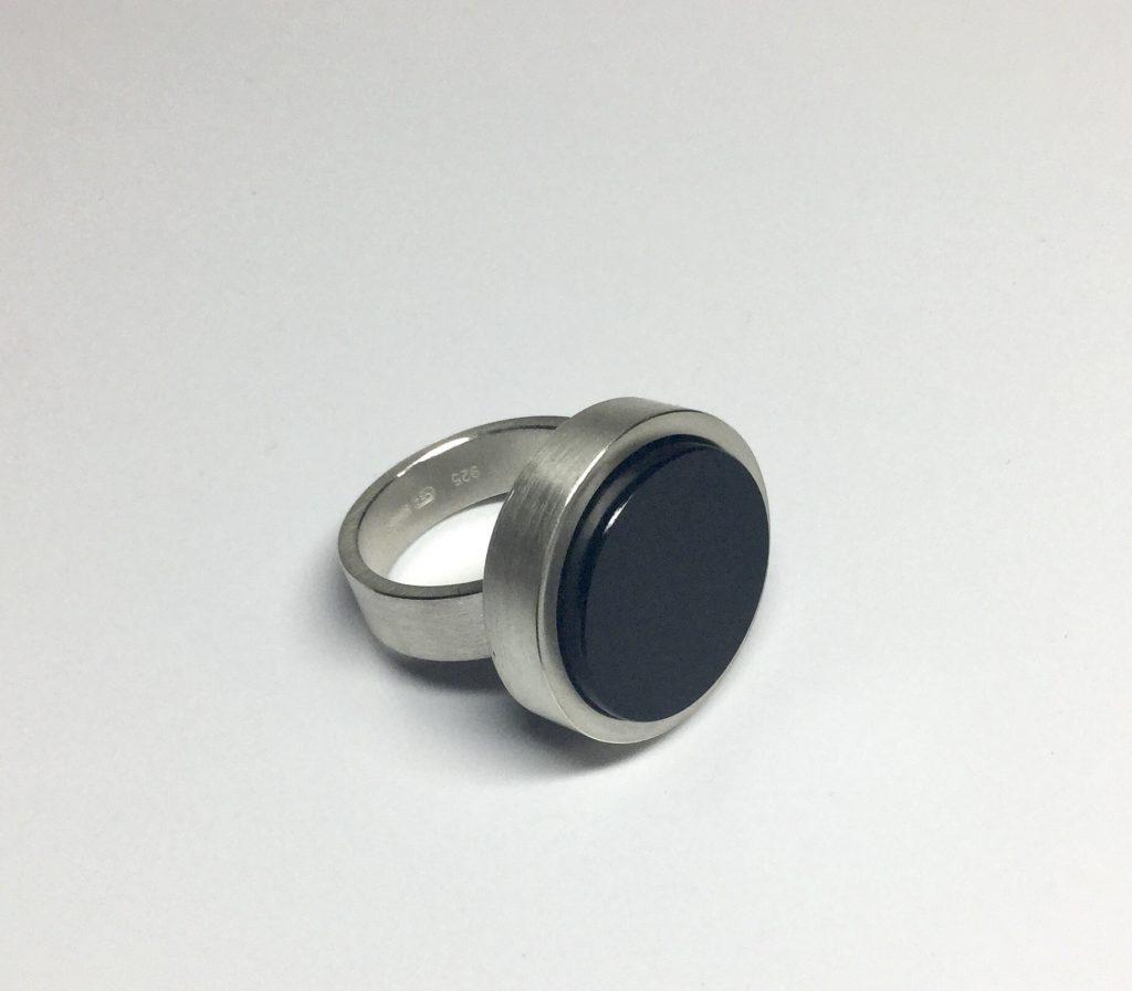 foto van een zilveren ring met een ronde zwarte onyx edelsteen.