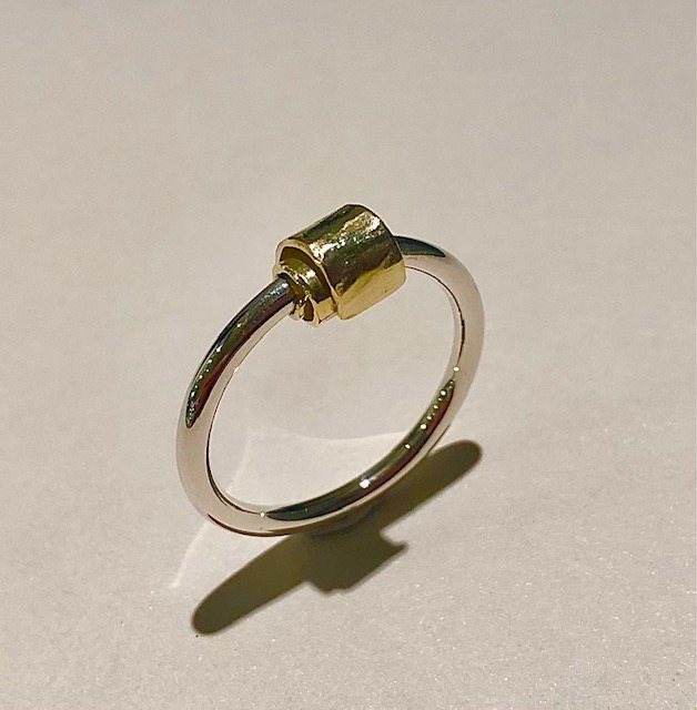 Foto van zilveren ring met gouden krul.