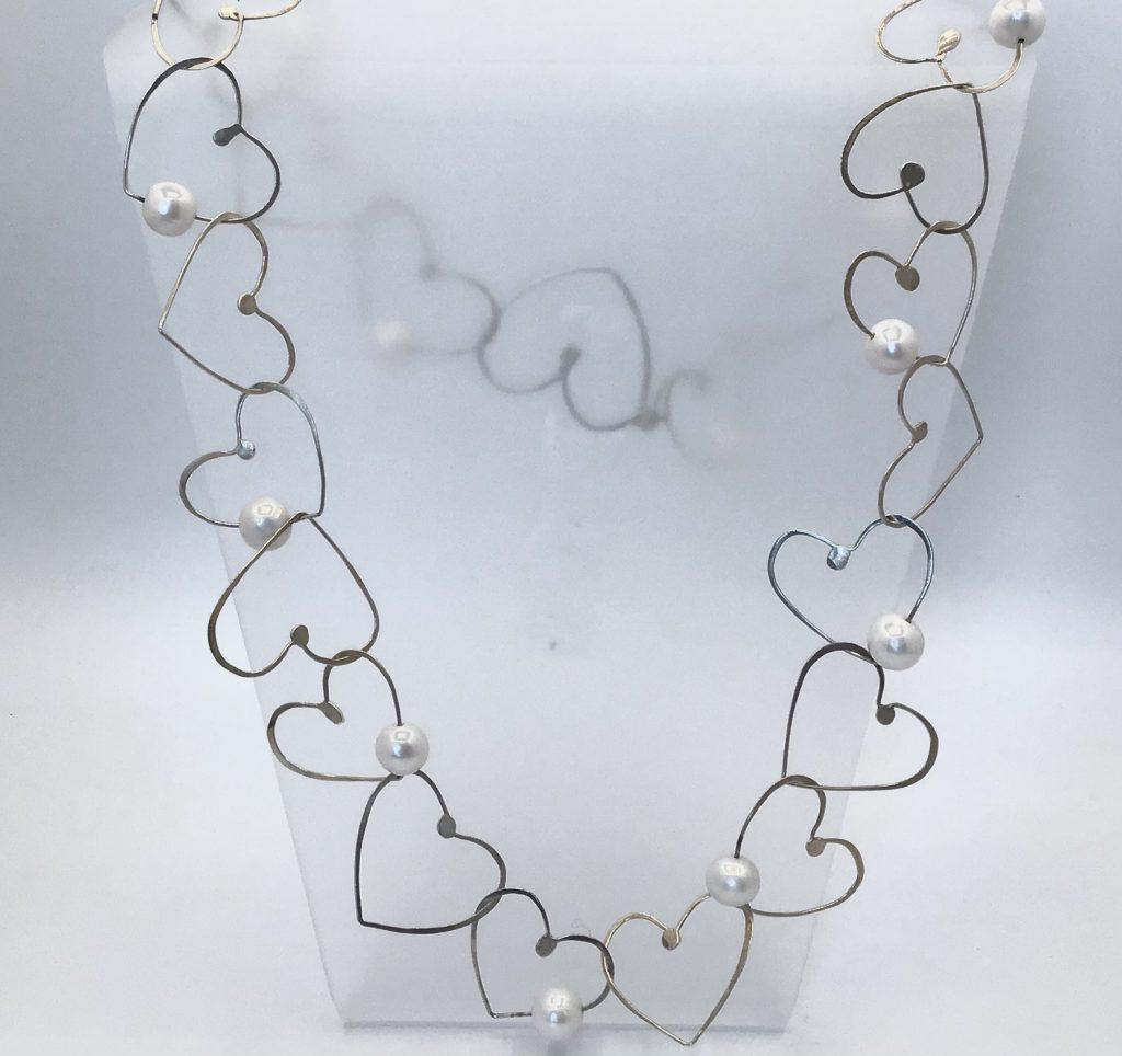 Foto van zilveren harten collier.