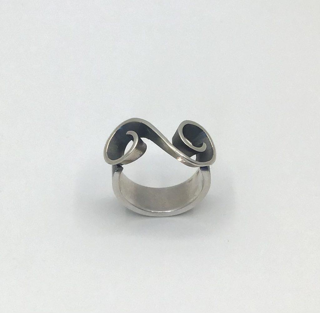 Foto van zilveren ring met sierlijke golf.